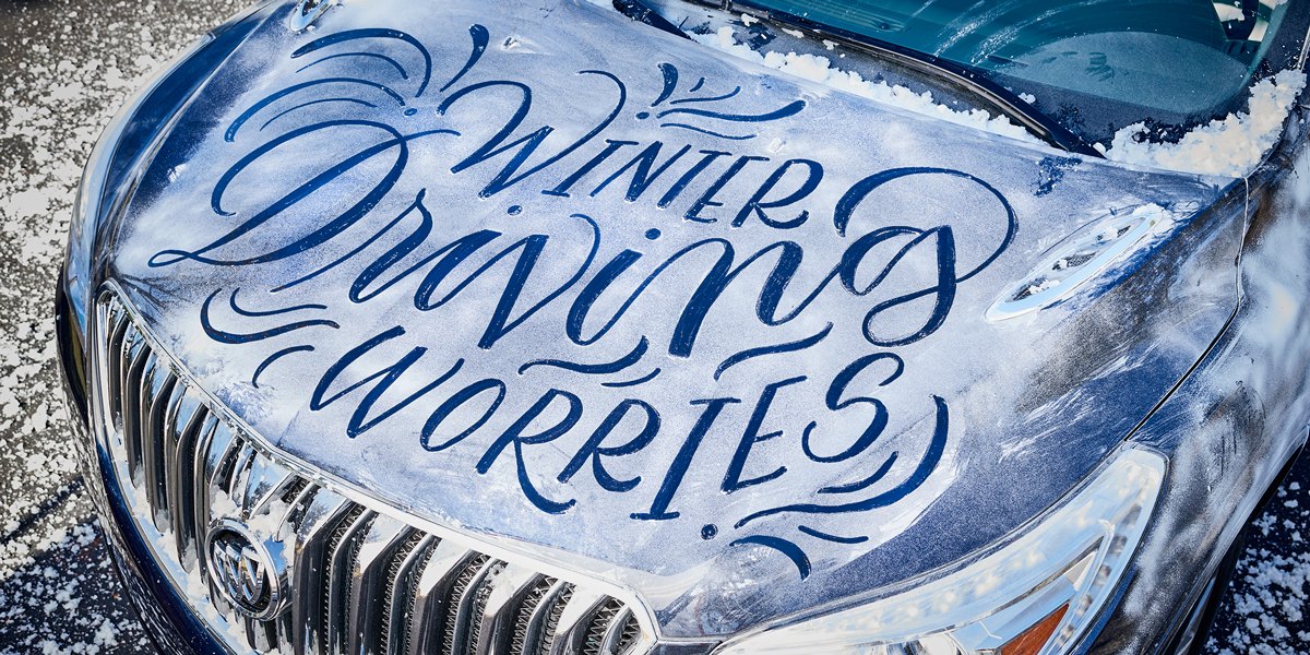 "Looking down at the hood of a blue Buick Enclave lightly covered in snow, with the words ""Winter Driving Worries"" written in the snow."